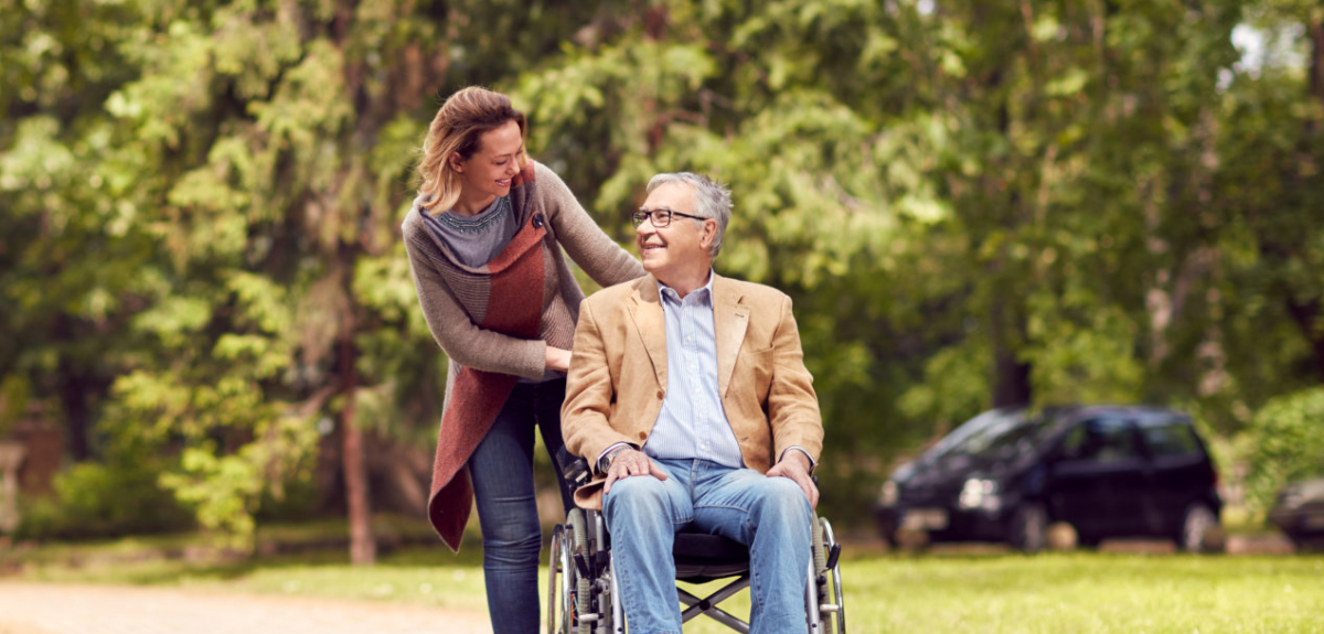 elderly man on a wheelchair and a woman behind him