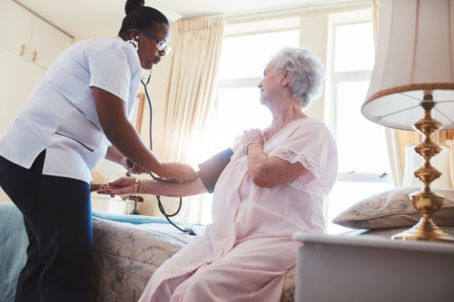 elderly woman having her blood pressure checked by a caregiver
