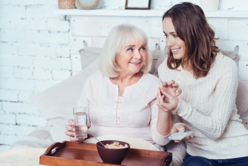 caregiver giving a medicine to a senior
